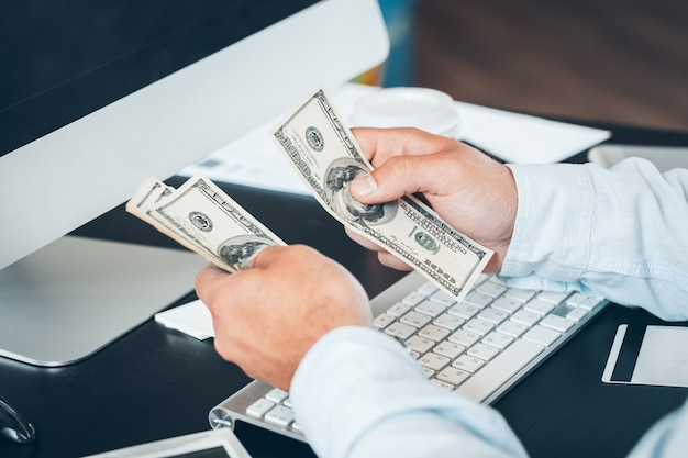 Mains caucasiennes comptant les billets en dollars