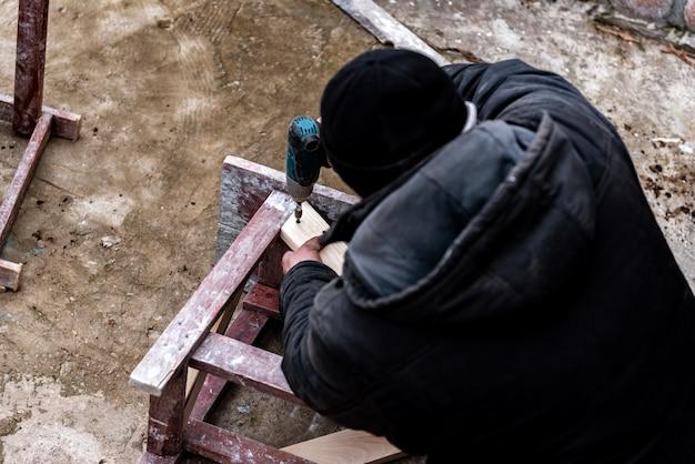 Mains de chaise de construction de vis de travailleur avec tournevis électronique en plein air.