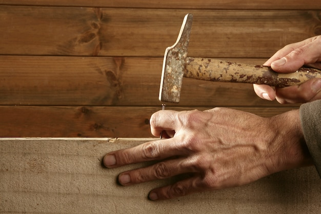 Mains de charpentier avec bois de marteau et clou
