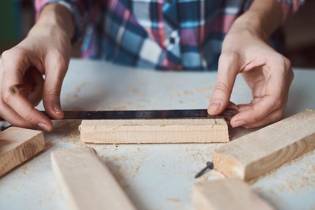 Mains de charpentier prenant une mesure avec un crayon de planche de bois.