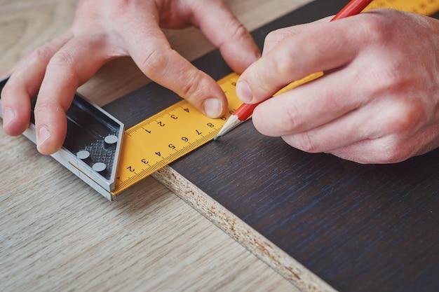 Mains charpentier, prendre, mesure, de, planche bois, gros plan