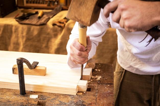 Mains de charpentier travaillant un morceau de bois
