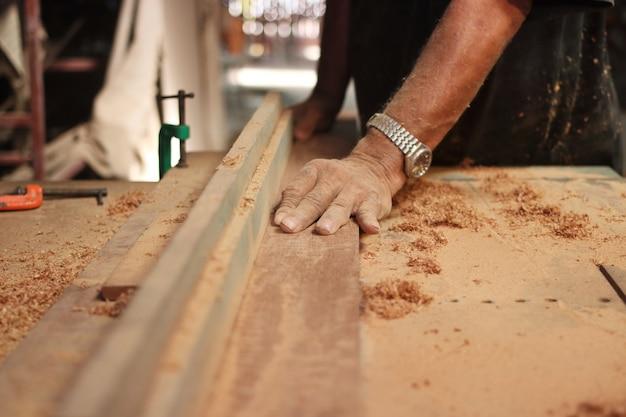 Mains de charpentier travaillant sur la table de toupie
