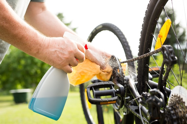Mains avec un chiffon et un garde-boue de vélo de nettoyage à l'eau