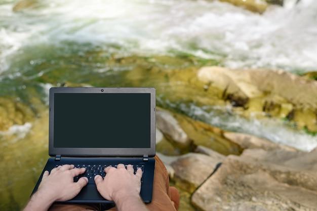 Mains sur le clavier d'ordinateur portable sur le fond d'une rivière