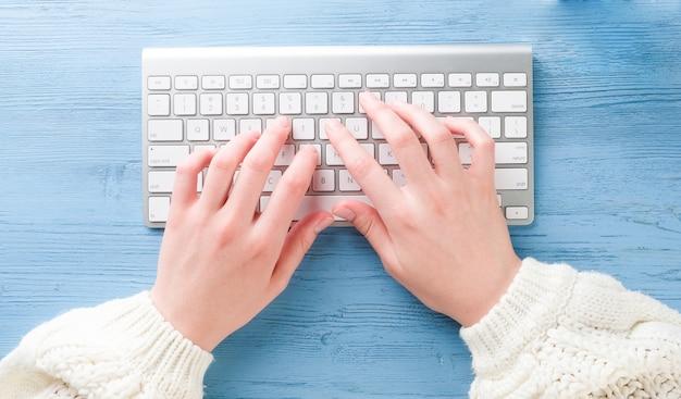Mains avec un clavier sur la table. une femme travaille sur un ordinateur.