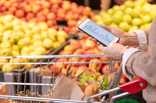 Mains de client féminin mature contemporain avec smartphone sur les produits alimentaires dans le panier à la recherche à travers la liste de courses