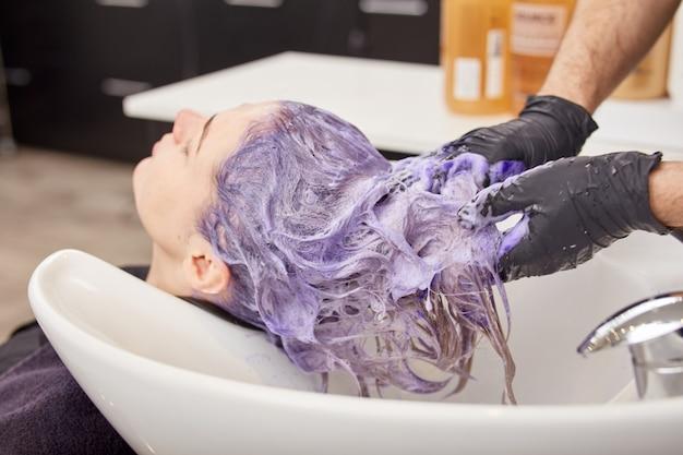 Mains de coiffeur appliquant un shampooing tonifiant sur les cheveux de la femme