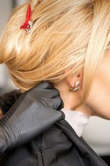 Mains de coiffeur faisant la préparation avant de donner la coupe de cheveux à la jeune femme blonde au salon de beauté
