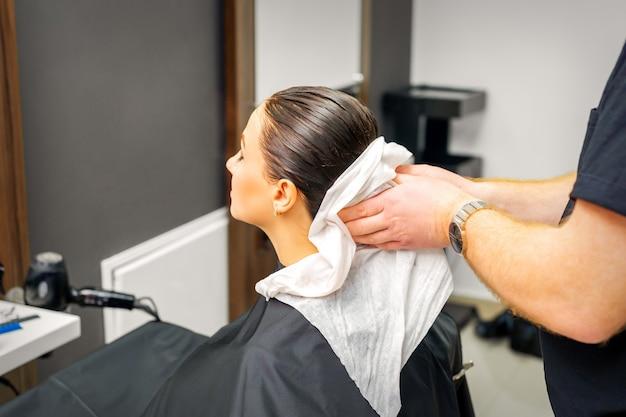 Les Mains D'un Coiffeur Masculin Essuient Les Cheveux D'une Cliente Avec Une Serviette Blanche Après Le Shampooing Dans Un Salon De Beauté Photo Premium