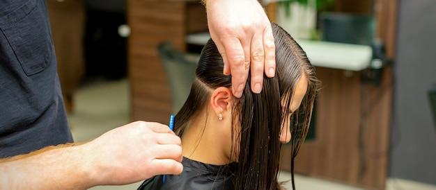 Mains d'un coiffeur peignant les cheveux d'une jeune femme séparés en sections au salon de coiffure