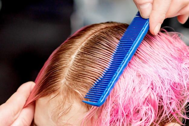 Mains coiffeur peigne les cheveux roses de la jeune femme se bouchent dans le salon de coiffure.