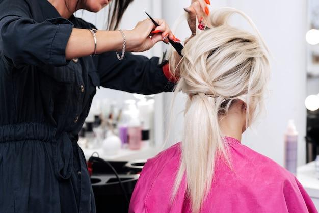 Les mains d'un coiffeur avec un peigne font une coiffure pour une fille blonde