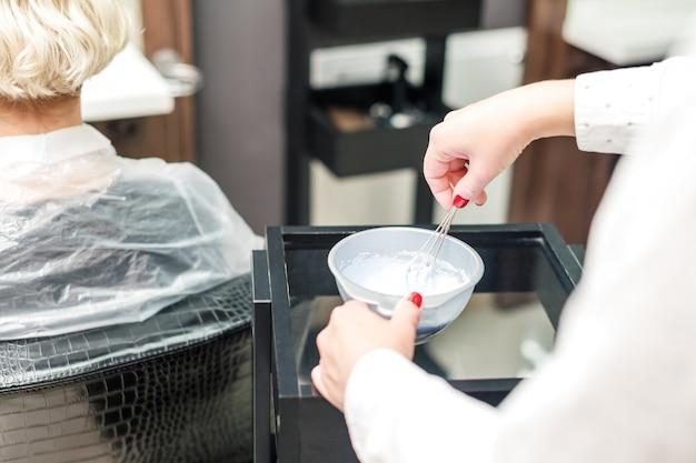 Les mains d'un coiffeur professionnel mélangent de la teinture pour les cheveux dans un bol.