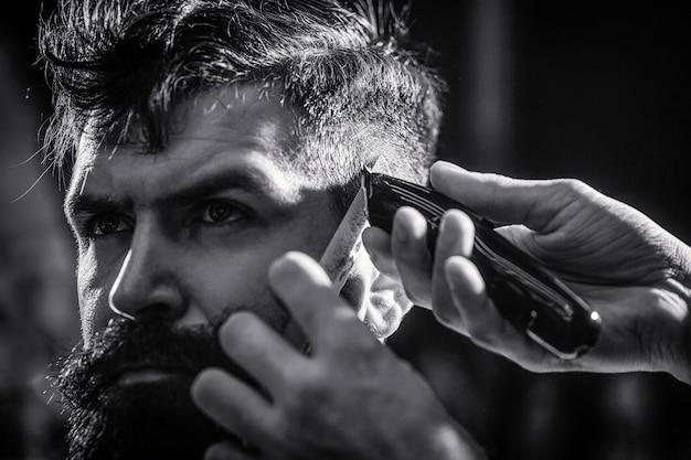 Mains de coiffeur avec tondeuse à cheveux. le coiffeur travaille avec une tondeuse à cheveux. client hipster se coupe les cheveux. notion de coupe de cheveux. homme visitant un coiffeur dans un salon de coiffure. noir et blanc.