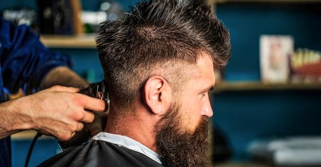 Mains de coiffeur avec tondeuse à cheveux, gros plan. concept de coupe de cheveux. homme visitant le coiffeur en salon de coiffure. barber travaille avec une tondeuse à cheveux. client hipster se coupe les cheveux.