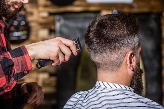 Mains de coiffeur avec tondeuse à cheveux, gros plan. notion de coupe de cheveux. client hipster se coupe les cheveux. homme visitant un coiffeur dans un salon de coiffure. le coiffeur travaille avec une tondeuse à cheveux. client hipster se coupe les cheveux