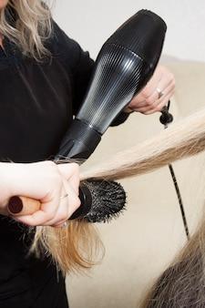 Mains de coiffeurs séchant de longs cheveux blonds
