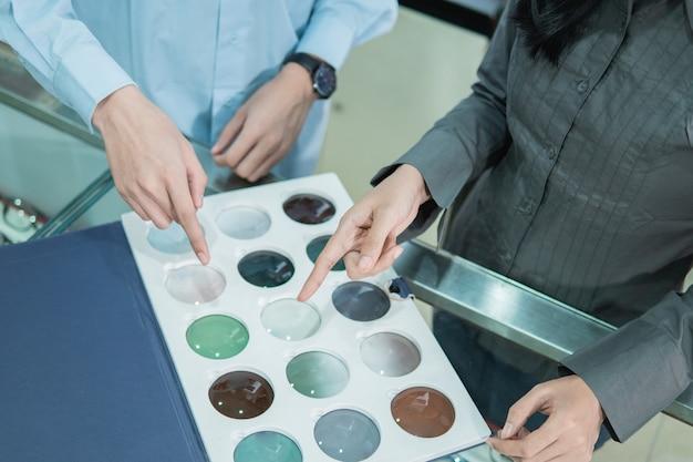 Les mains d'un commerçant et d'un client pointant du doigt un échantillon de lentilles lors de la sélection du type de lentille chez un opticien