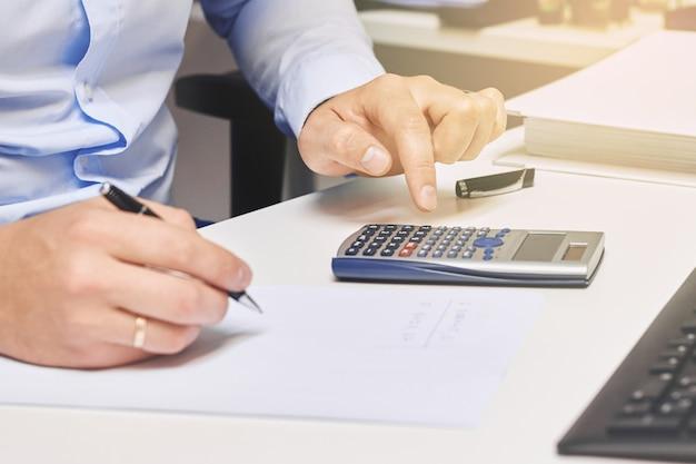 Mains de comptable travaillant avec la calculatrice dans le bureau