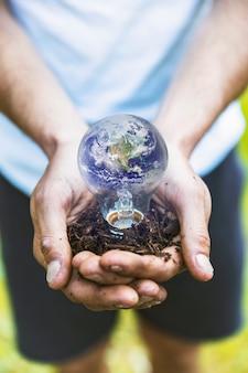 Mains de concept tenant la terre dans le bulbe