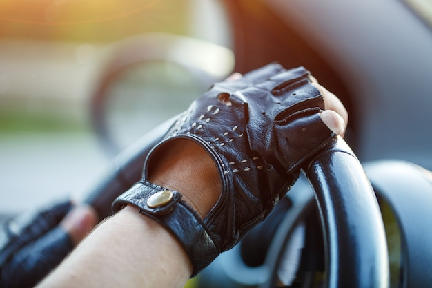 Les mains des conducteurs dans des gants en cuir conduisant une femme de voiture en mouvement tenant le volant dans des gants de course