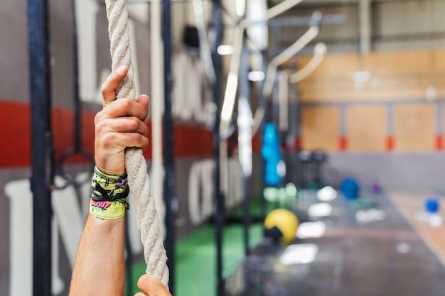 Mains sur la corde dans la salle de gym