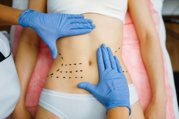 Les mains de la cosméticienne sur l'abdomen de la patiente, préparation de thérapie botox. procédure de rajeunissement dans un salon d'esthéticienne. chirurgie esthétique contre les rides et le vieillissement