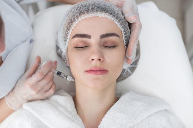 Mains de cosmétologue faisant l'injection dans le visage, les lèvres. jeune femme reçoit des injections faciales de beauté dans le salon. procédures de vieillissement, de rajeunissement et d'hydratation du visage. cosmétologie esthétique.