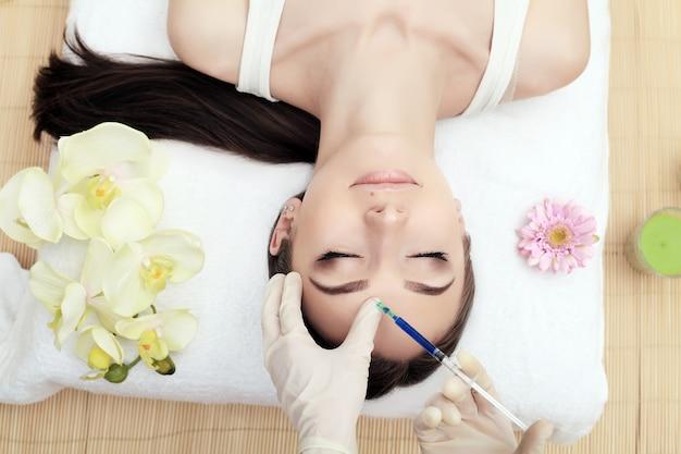 Mains, cosmétologue, injection, figure, jeune femme, beauté, injections faciales, dans, salon
