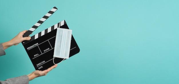 Les mains avec un costume gris tiennent un panneau de clapet noir ou un masque facial en ardoise de film sur fond vert menthe