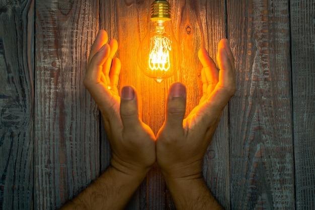 Les mains à côté d'une ampoule allumée