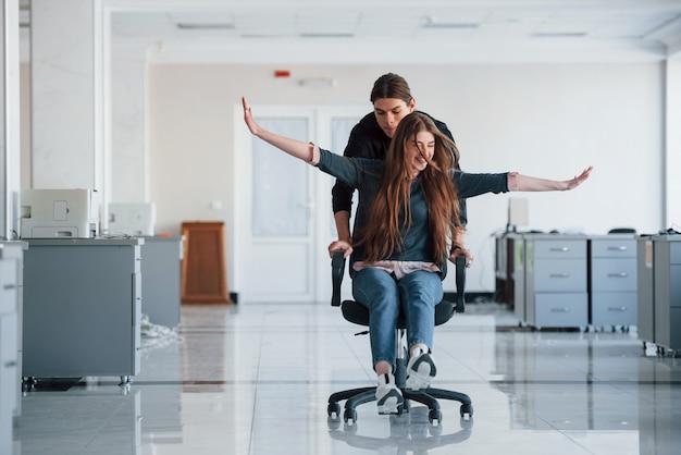Avec les mains sur les côtés. s'amuser au bureau. les jeunes font une pause et conduisent en utilisant un siège