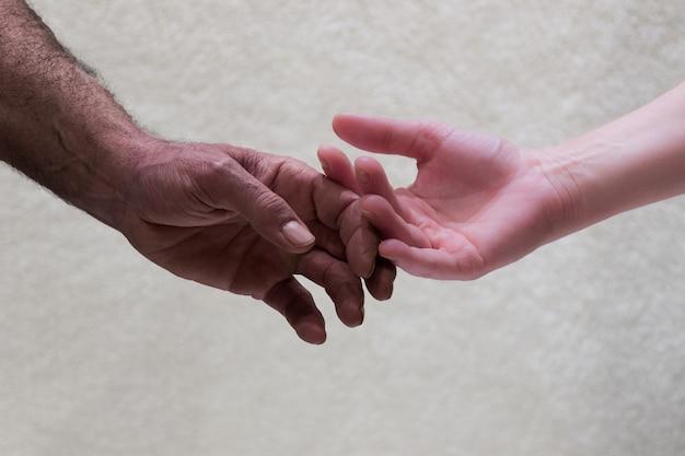 Les mains de couleur de peau différente approchant