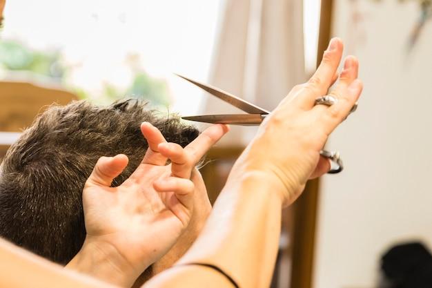 Mains coupant les cheveux d'un homme