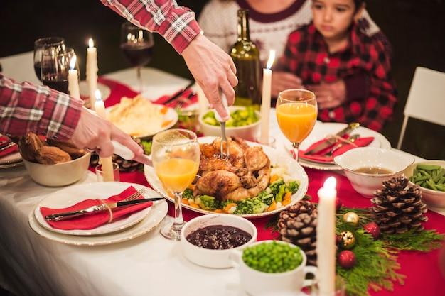 Mains coupant la dinde au dîner de noël