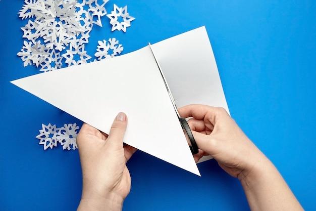 Mains coupant une feuille de papier blanc pour faire des flocons de neige