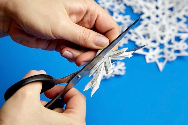 Mains coupant des flocons de neige en papier blanc
