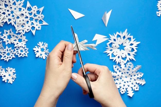 Mains coupant des flocons de papier blanc sur fond bleu