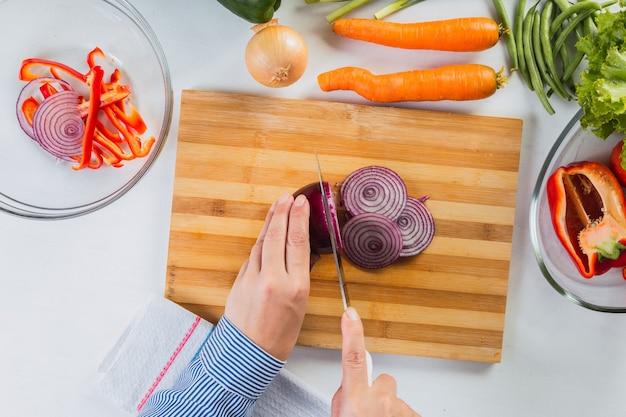 Mains coupant les oignons dans la cuisine.