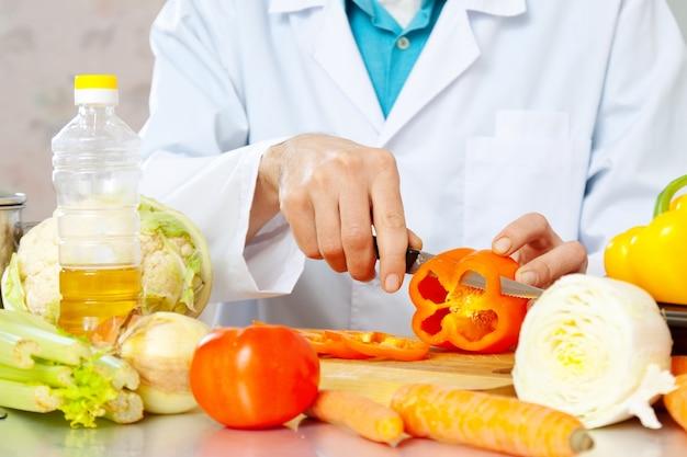 Les mains coupent les légumes