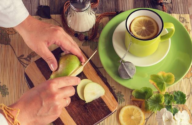 Les mains coupent une poire. ensuite, thé au citron dans une tasse verte, un sucrier, une planche avec une poire verte et un couteau. photo atmosphérique. couleurs vives fraîches. vue de dessus.