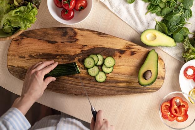 Mains couper le concombre sur une planche de bois