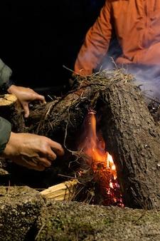 Mains d'un couple adulte allumant un feu de camp la nuit au milieu de la forêt