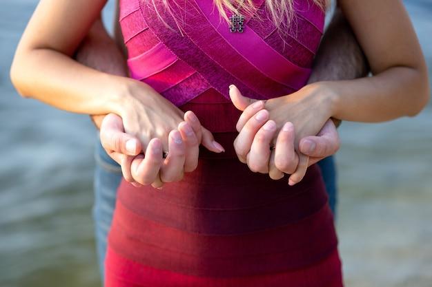 Mains d'un couple amoureux ensemble sur fond d'eau