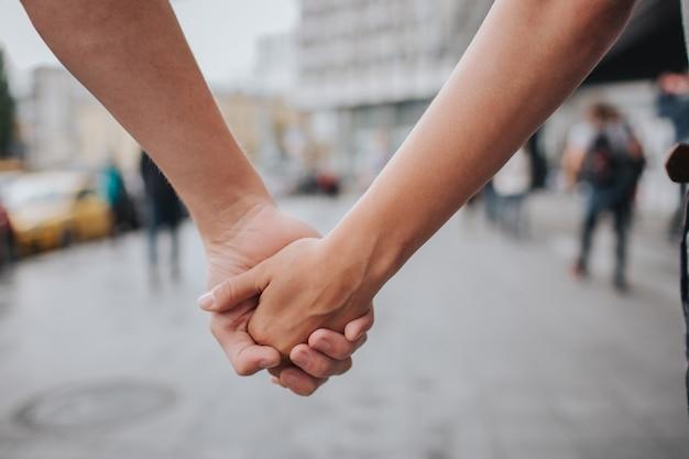 Mains de couple fermées ensemble à l'extérieur dans une relation amoureuse et romantique. gros plan du corps. homme et femme dans la ville.