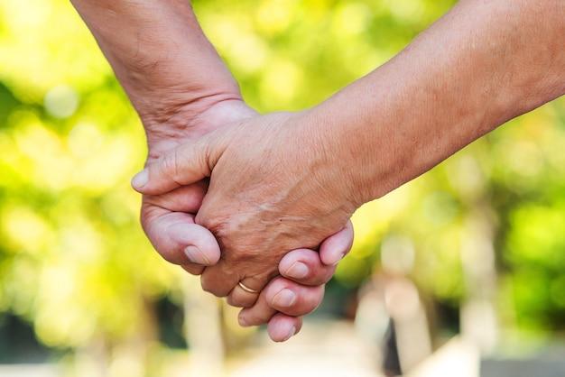 Mains d'un couple de personnes âgées, gros plan. couple de personnes âgées se tenant la main pendant la marche. notion d'amour. concept de prendre soin de mûrir ensemble.