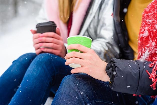 Mains de couple avec des tasses de boissons chaudes close-up
