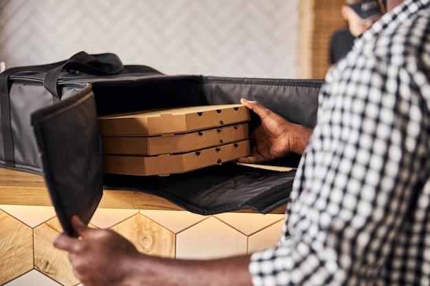 Mains de courrier mâle plaçant des boîtes à pizza en carton dans un sac d'emballage thermique isolé