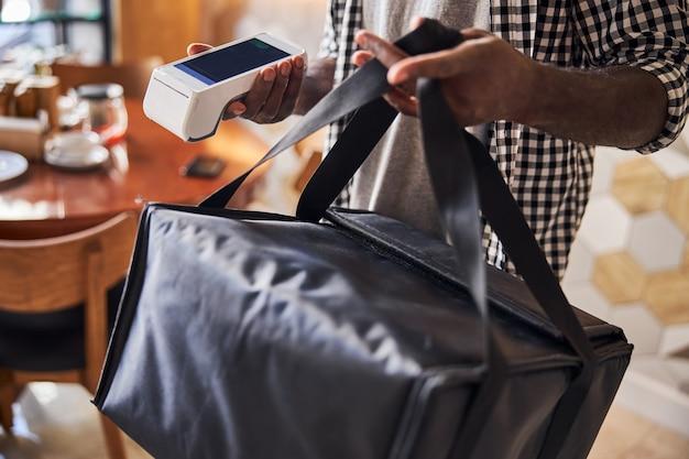 Mains de courrier masculin tenant un sac d'emballage thermique isolé et un lecteur de carte sans contact